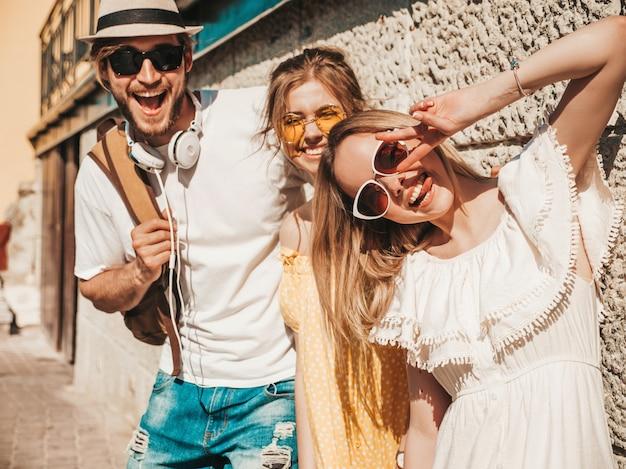 Grupo de jovens três amigos elegantes posando na rua. homem moda e duas miúdas giras vestidas com roupas de verão casual. modelos sorridentes se divertindo em óculos de sol. mulheres alegres e cara mostram a língua