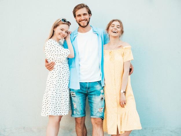 Grupo de jovens três amigos elegantes posando na rua. homem moda e duas miúdas giras vestidas com roupas de verão casual. modelos sorridentes se divertindo perto da parede. mulheres alegres e cara ao ar livre