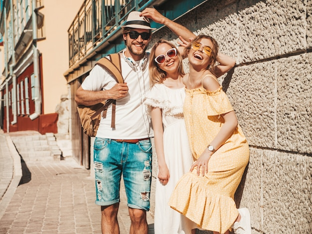 Grupo de jovens três amigos elegantes posando na rua. homem moda e duas miúdas giras vestidas com roupas de verão casual. sorrindo modelos se divertindo em óculos de sol. mulheres alegres e cara ao ar livre