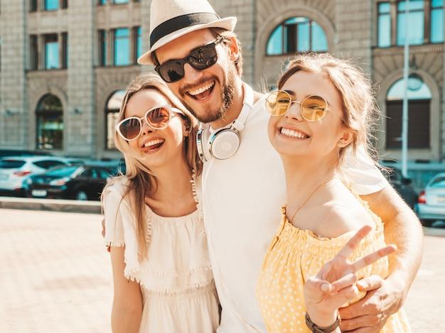 Grupo de jovens três amigos elegantes posando na rua. homem moda e duas miúdas giras vestidas com roupas de verão casual. sorrindo modelos se divertindo em óculos de sol. mulheres alegres e cara enlouquecendo