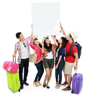Grupo de jovens turistas segurar uma bandeira branca e olhar para cima