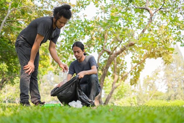 Grupo de jovens voluntários asiáticos pegando lixo no parque.