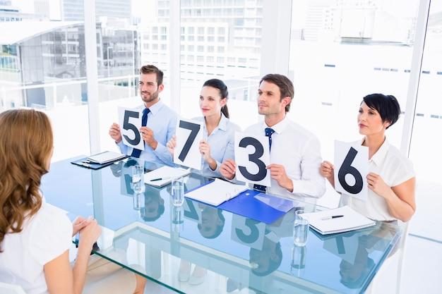 Grupo de juízes do painel que mantém sinais de pontuação na frente da mulher