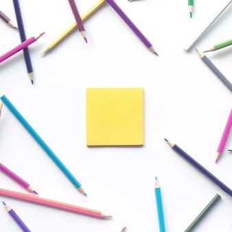 Grupo de lápis colorido com fundo de papel de nota de espaço de cópia.