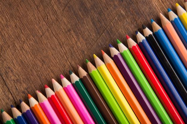 Grupo de lápis coloridos no conceito de ferramenta de equipamento de galeria de arte de fundo mesa de madeira