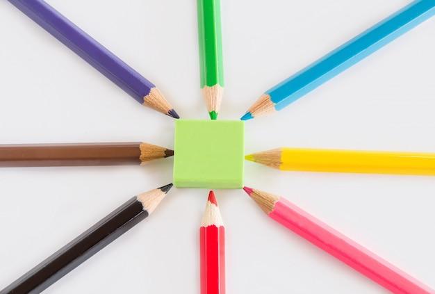 Grupo de lápis de grafite e cor, borracha verde sobre fundo branco, com cópia do espaço