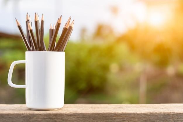 Grupo de lápis no copo de café branco.