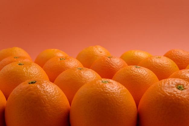 Grupo de laranjas em uma fileira em fundo laranja.