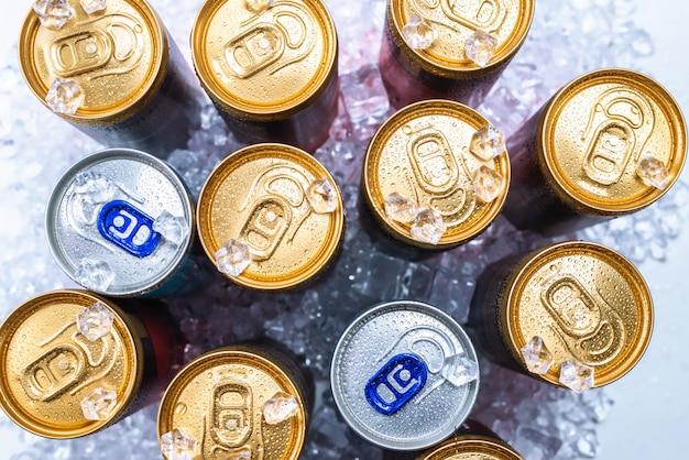 Grupo de latas de alumínio no gelo, bebida gelada.