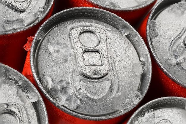 Grupo de latas de refrigerante de alumínio vermelho no gelo com gotas de água