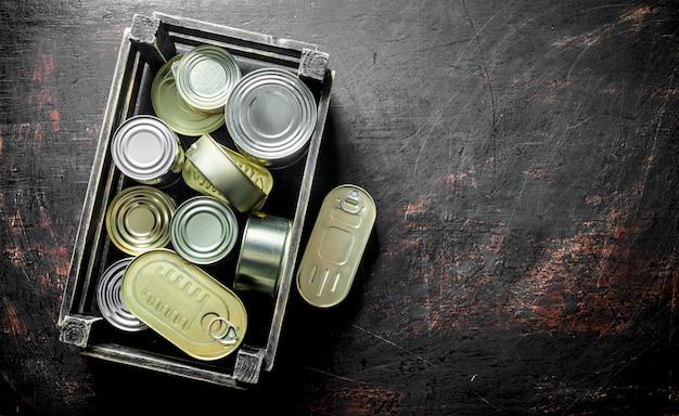 Grupo de latas fechadas de alumínio com comida enlatada em uma caixa. em fundo escuro rústico