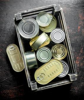 Grupo de latas fechadas de alumínio com comida enlatada em uma caixa. na superfície rústica escura