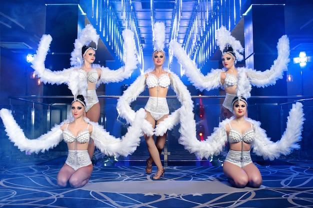 Grupo de lindas dançarinas em fantasias de carnaval branco