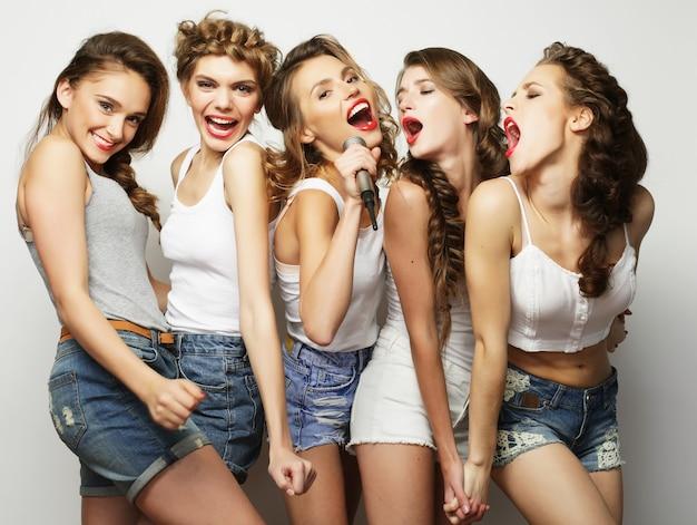 Grupo de lindas garotas elegantes e hipster cantando karaokê