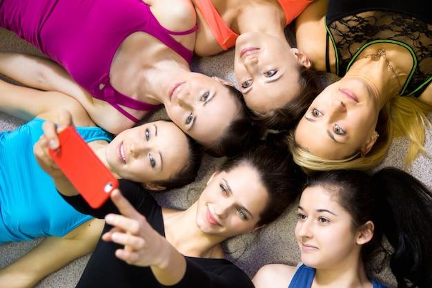 Grupo de lindas namoradas desportivas tomando selfie, auto-retrato com smartphone vista do topo