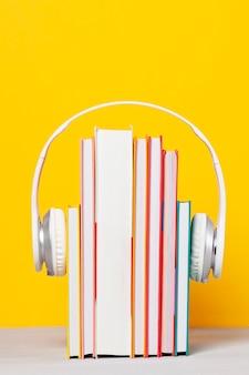 Grupo de livros com os fones de ouvido. conceito de audiolivros