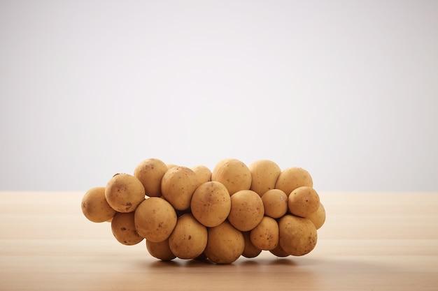 Grupo de longkong é uma fruta do sul da ásia tailandesa na mesa de madeira copie o espaço para o texto