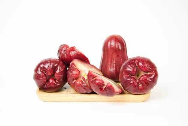 Grupo de maçã rosa ou maçã java em uma bandeja de madeira no fundo branco.