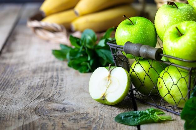Grupo de maçãs verdes saudáveis, bananas e hortelã são ingredientes para um smoothie