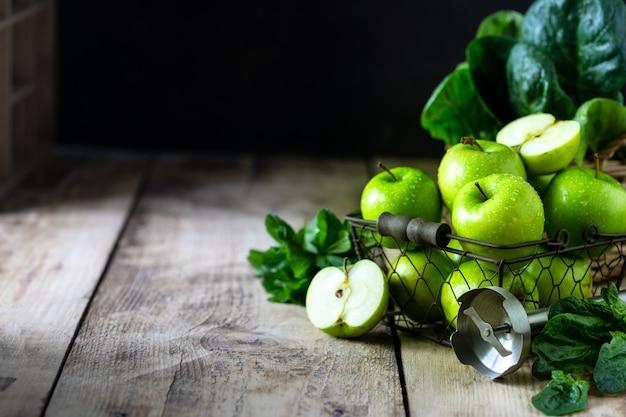 Grupo de maçãs verdes saudáveis, espinafre, banana e hortelã são ingredientes para um smoothie. desintoxicação, dieta, saudável, conceito de comida vegetariana. espaço livre para texto. copie o espaço.