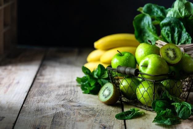 Grupo de maçãs verdes saudáveis, espinafre, kiwi, banana e hortelã são ingredientes para um smoothie. copie o espaço.