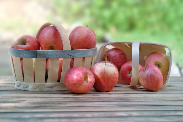 Grupo de maçãs vermelhas em pequenas cestas em uma mesa de madeira no jardim sobre fundo verde