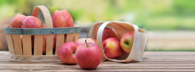 Grupo de maçãs vermelhas em uma pequena cesta sobre uma mesa de madeira no jardim sobre fundo verde