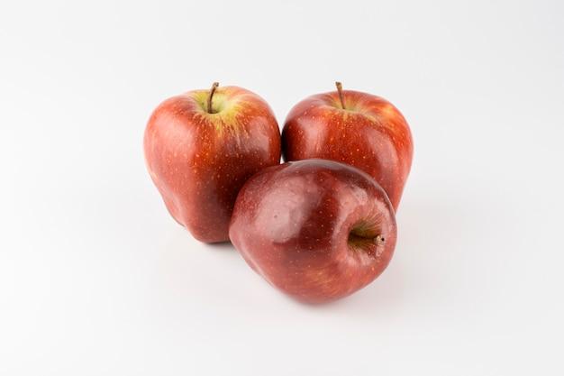 Grupo de maçãs vermelhas sobre fundo branco.