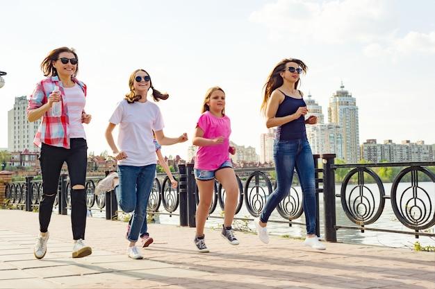 Grupo de mães e filhas estão correndo ao longo da estrada no parque