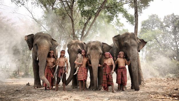 Grupo de mahouts e elefantes na floresta Foto Premium
