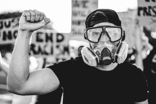 Grupo de manifestantes na estrada de diferentes culturas lutam pelos direitos humanos - foco na máscara de gás