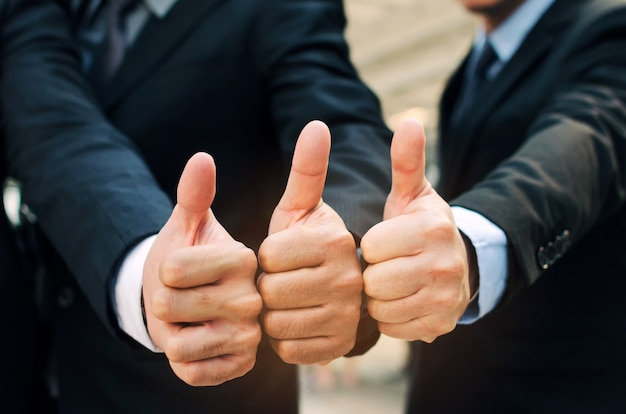 Grupo de mão de equipe de pessoas de negócios bonito em terno mostrando os polegares juntos