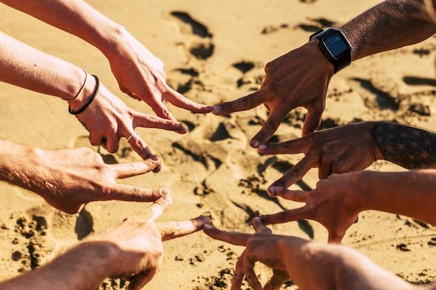 Grupo de mãos brancas fazendo sinal de vitória sob o dia ensolarado