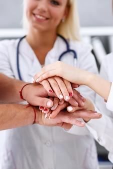 Grupo de médico cruzou as mãos na pilha para vitória