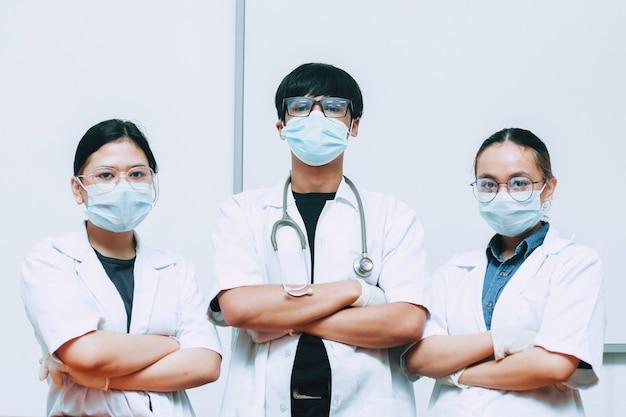 Grupo de médico usando máscara protetora e uniforme posando com confiança