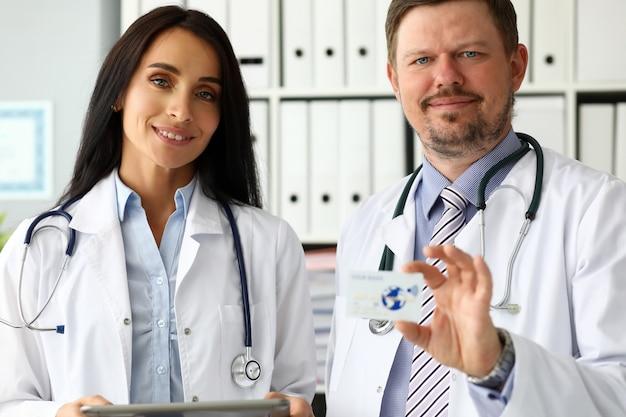 Grupo de médicos caucasianos maduros sorridentes, oferecendo cartão de plástico especial