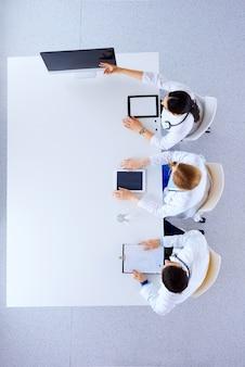 Grupo de médicos com comprimidos e computadores na discussão do hospital e mostra algo sobre o conceito de tela-medicina, saúde e cardiologia. vista plana leiga, superior.