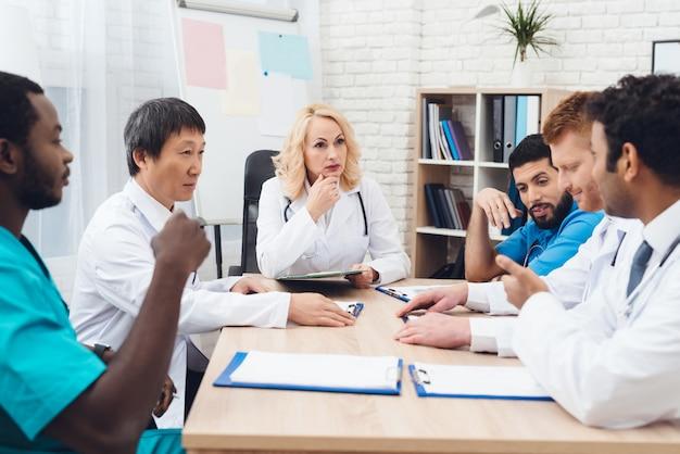 Grupo de médicos de diferentes raças é reunião em uma mesa.