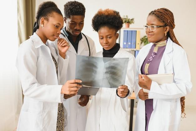 Grupo de médicos em consultório com raio-x do paciente