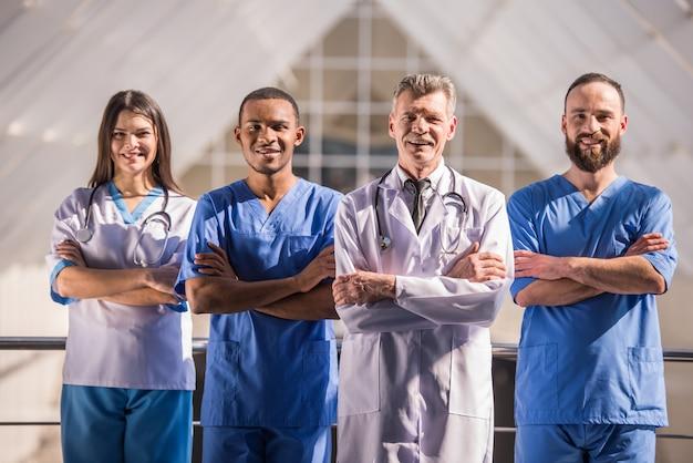 Grupo de médicos em pé com os braços cruzados no hospital.