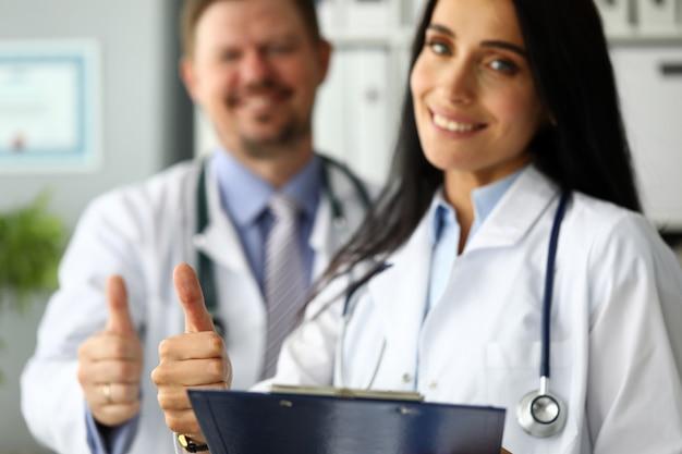 Grupo de médicos em pé na fila, aparecendo o polegar