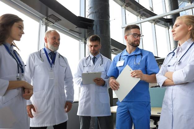 Grupo de médicos em pé no consultório médico.