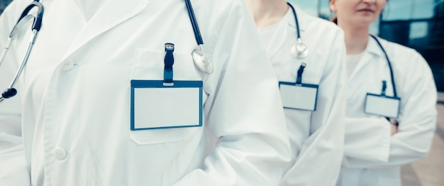 Grupo de médicos especialistas com crachás em branco em uma fileira de perto