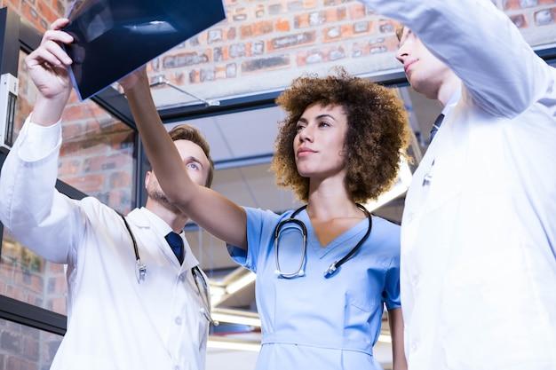 Grupo de médicos examinando relatório de machado no hospital