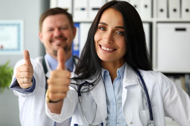 Grupo de médicos felizes sorrindo, mostrando o dedo no símbolo