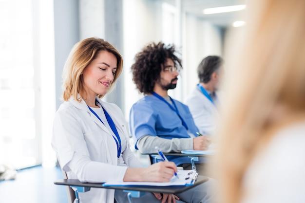 Grupo de médicos irreconhecíveis na conferência, equipe médica sentada e ouvindo.
