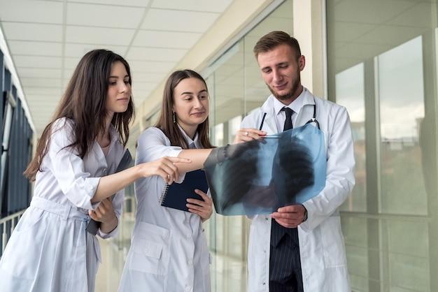 Grupo de médicos que examinam os pulmões de raios-x para prescrever um tratamento eficaz para o novo vírus covid19. epidemia