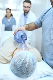 Grupo de médicos realizando reanimação com desfibrilador do paciente no hospital