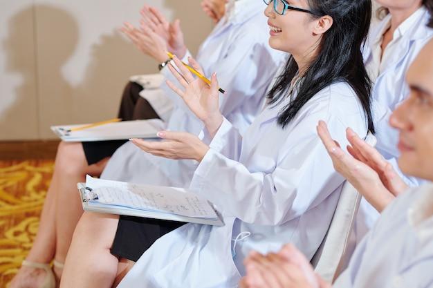 Grupo de médicos sorridentes aplaudindo o palestrante em conferência médica