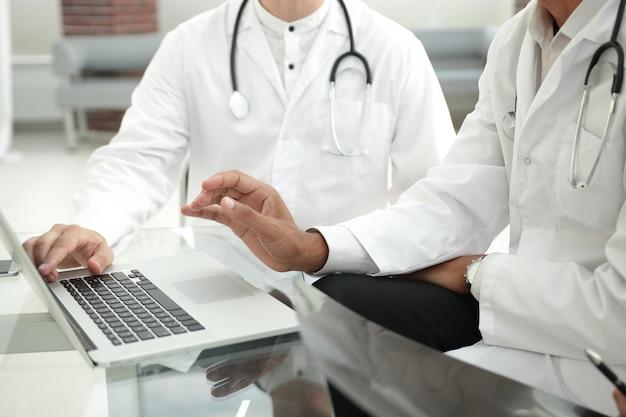 Grupo de médicos usando um laptop em uma reunião de trabalho.